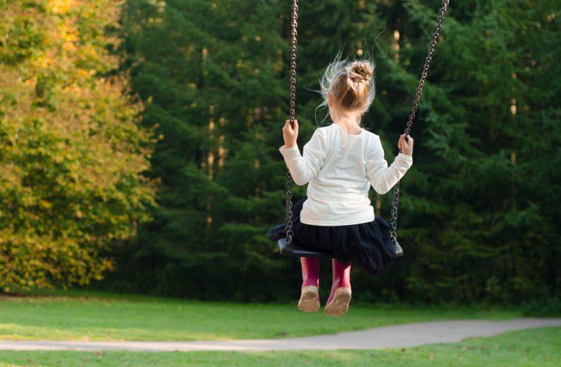back of girl on swing