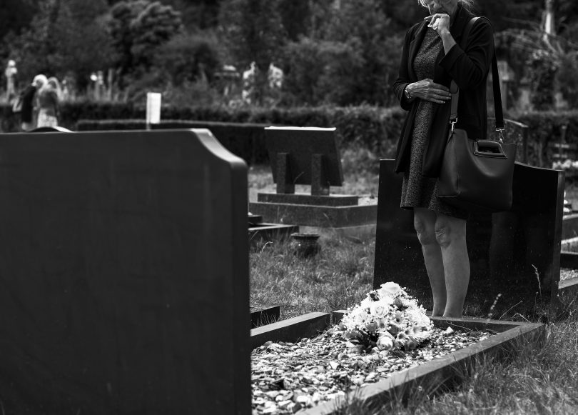 black and white woman standing alone at grave in cemetery mourning