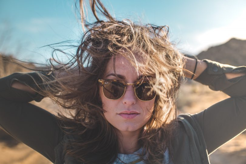 woman sunglasses wind blow hair desert