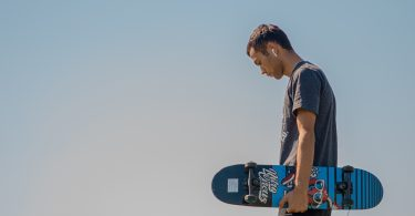 tan young adult man holding skateboard looking down sky background sad