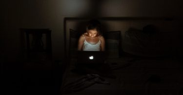 girl in dark on bed on laptop