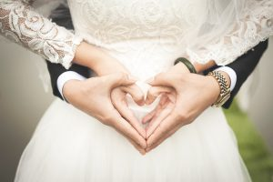 groom and bride hands form heart shape on wedding dress midriff