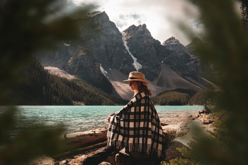 woman wearing plaid blanket and hat sitting in alberta nature
