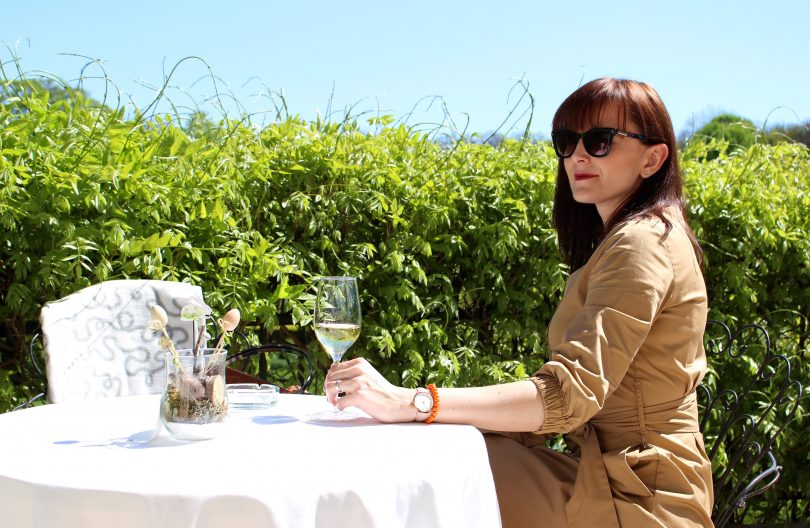woman in trench coat and sunglasses drinking white wine