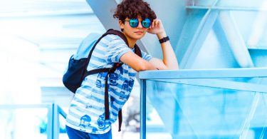 boy wearing blue circle shades leaning pose on glass wall