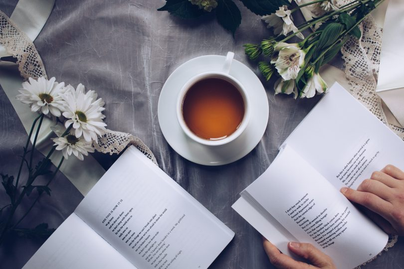 white aesthetic coffee books flowers on bed