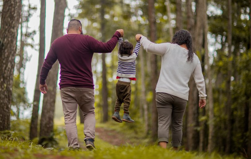 mom and dad lift up child boy forest