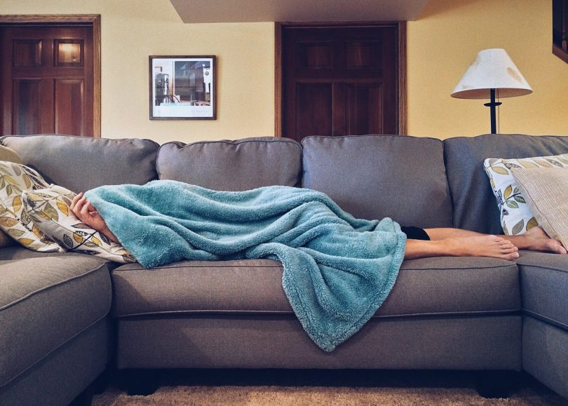 barefoot woman lying on couch with blanket covering her face