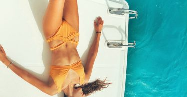 woman in yellow bikini on white boat aqua water tanning
