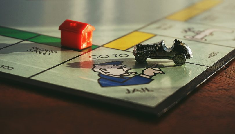 monopoly board car on go to jail next to red house