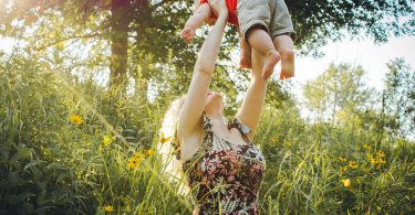 mom lifting child in field
