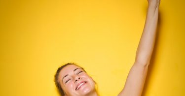 woman celebrating arm up smile
