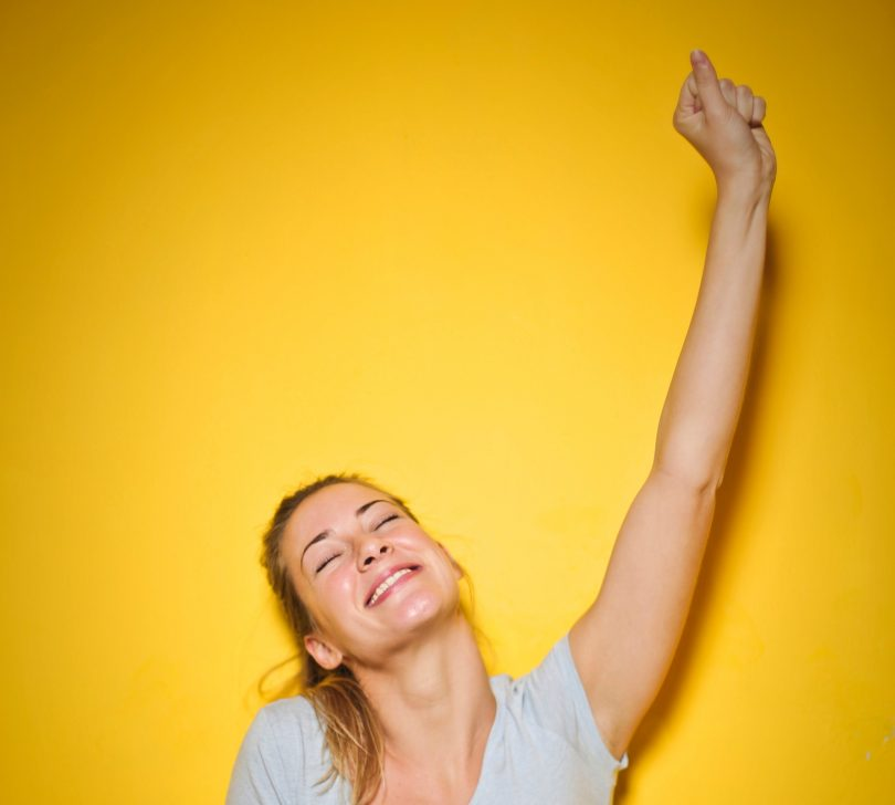 woman celebrating arm up smile