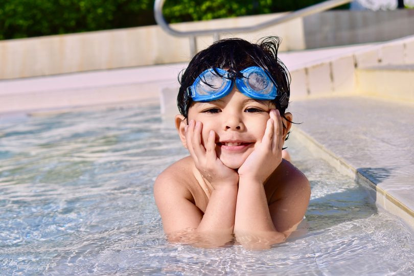 boy in pool with google on head