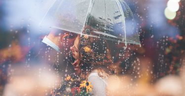 couple kissing rain umbrella