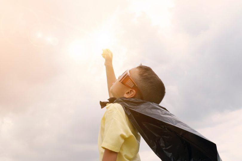 boy superhero hand up sky sun