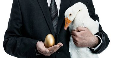 man in suit holding white goose and golden egg