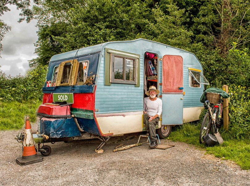 old man sitting in camper doorway colourful
