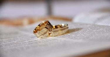two gold wedding rings on certificate