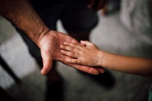 Child hand on fathers palm