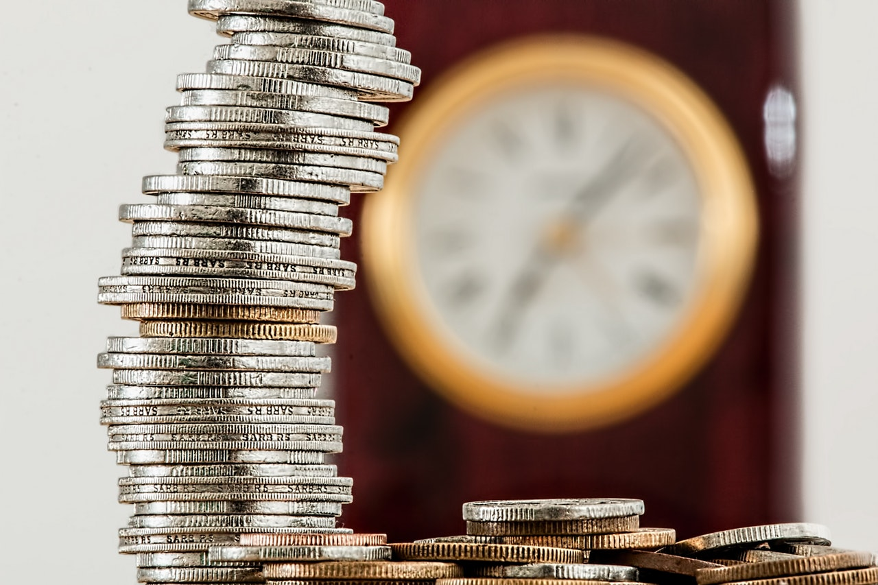 coins stacked in front of a clock