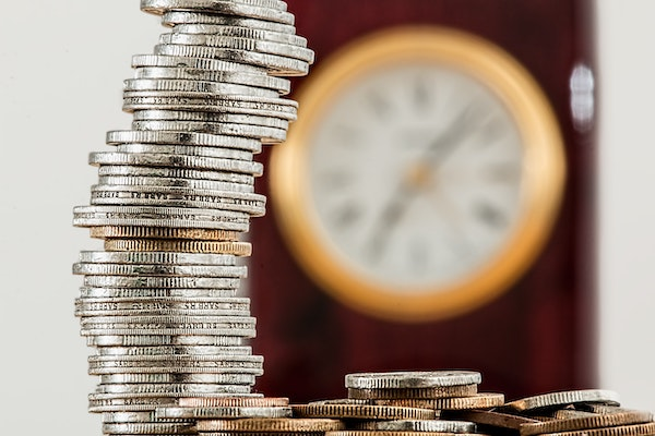 coins stacked in front of out of focus clock