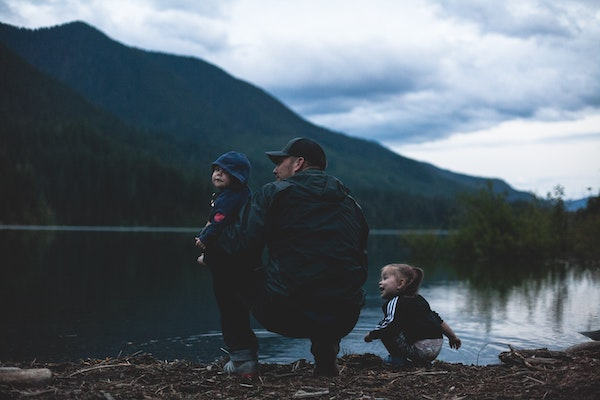 man with two children at lake and mountain
