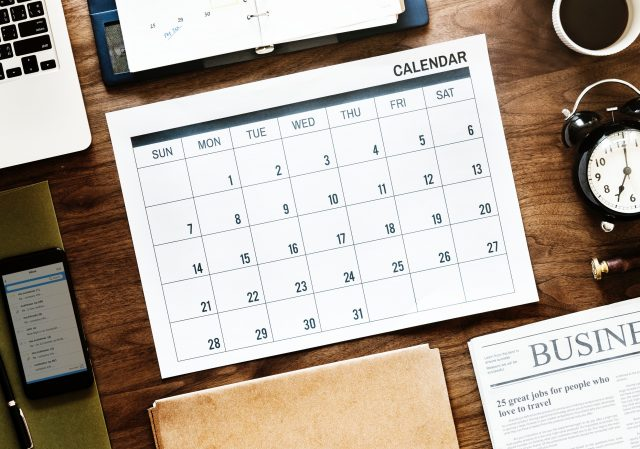 empty calendar page on desk surrounded by phone laptop newspaper clock