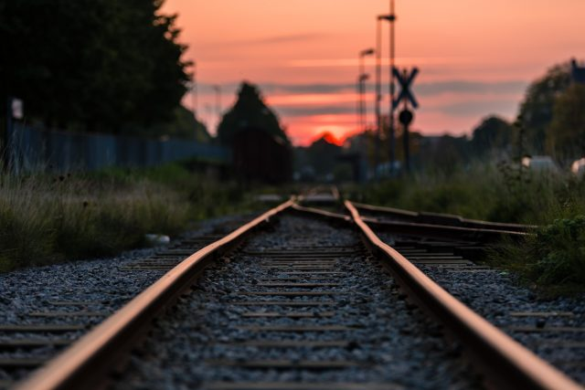 low angle train tracks leading to pink sunset