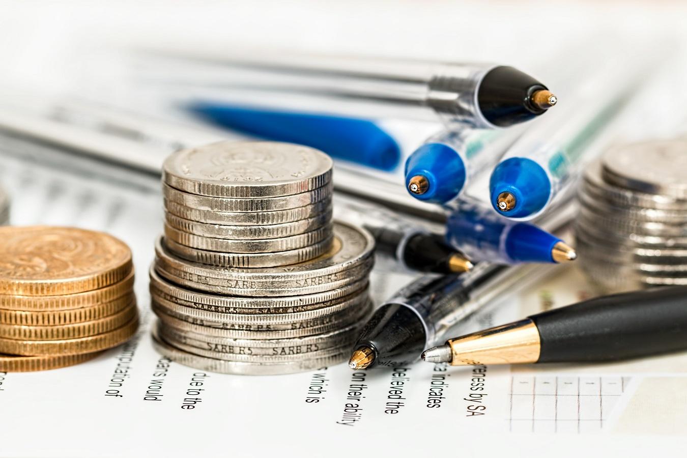 coins beside pens