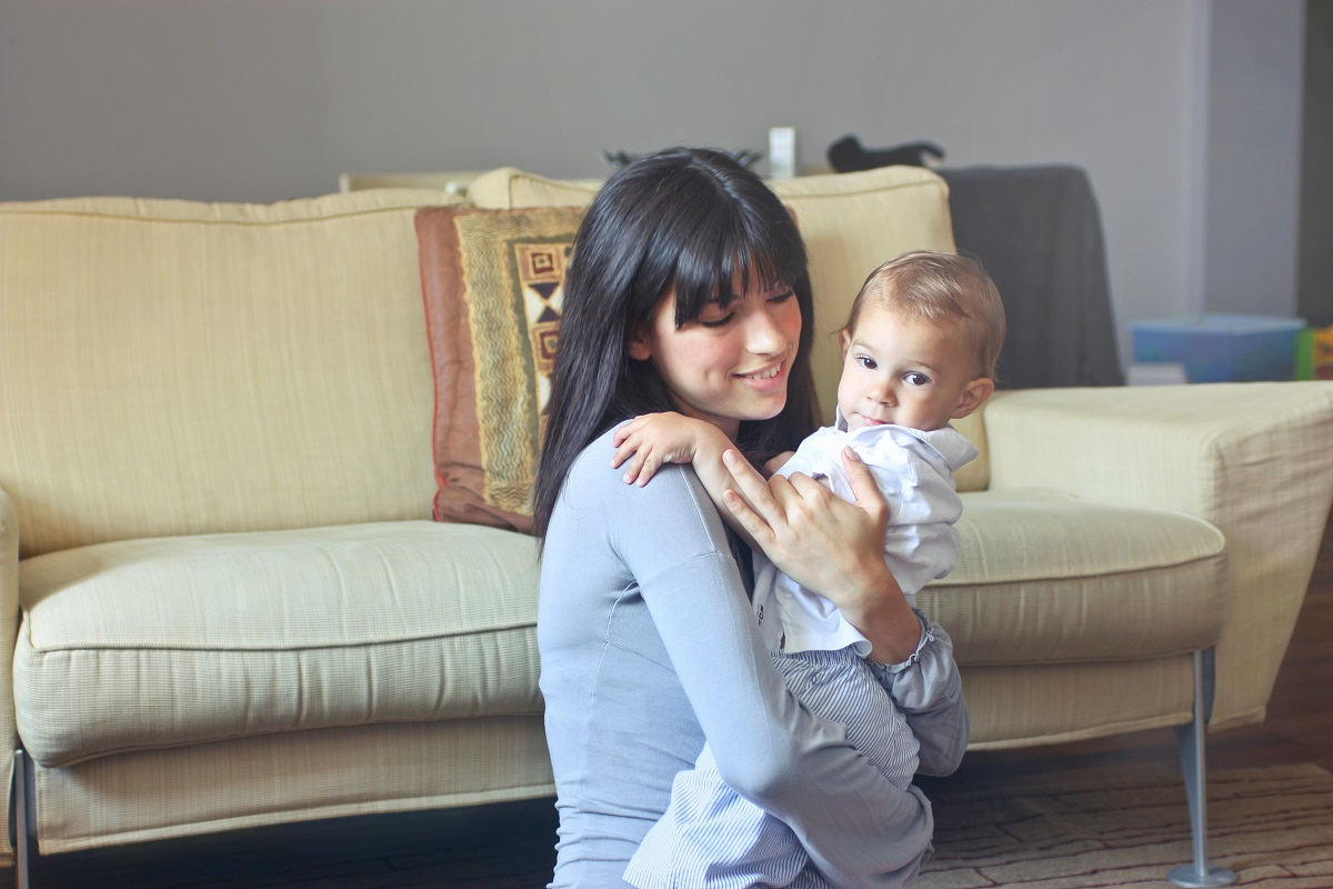 Woman-in-Gray-Sweater-Carrying-Toddler-in-White-Button-up-Shirt