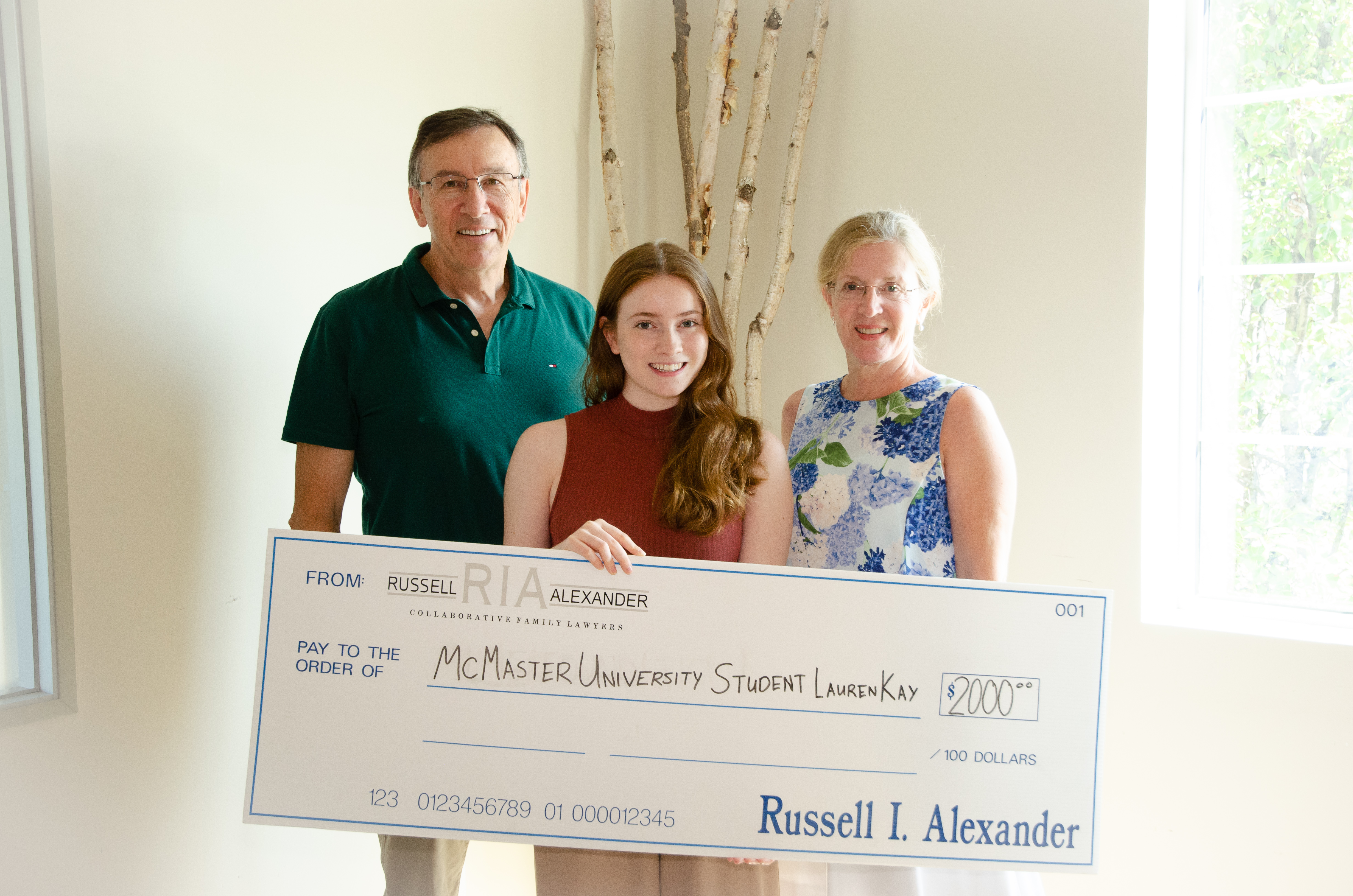daughter holding cheque smiling with parents