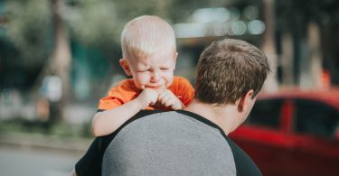 dad carry crying boy to car