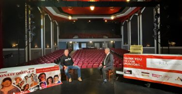 interview on stage in old theatre with empty seats