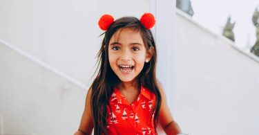 young girl child red dress smile holding ipad
