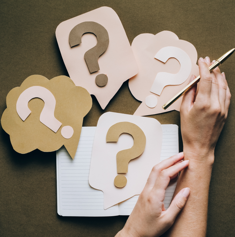 question marks with woman holding a pen