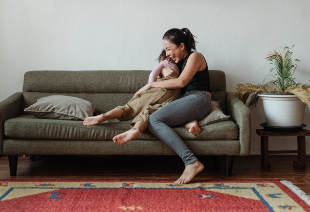 mom and child hugging and laughing on couch